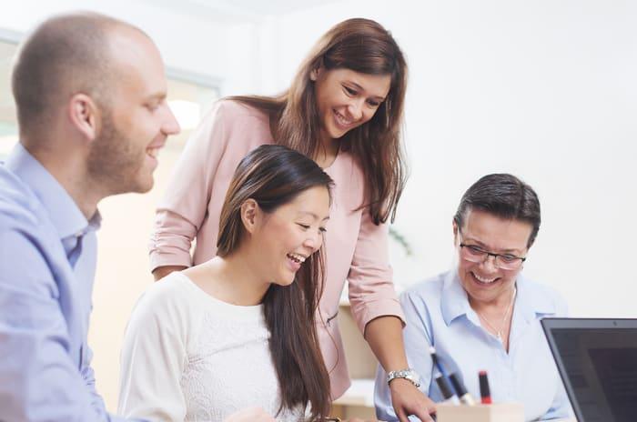Fire personer som ser på samme skjerm og smiler