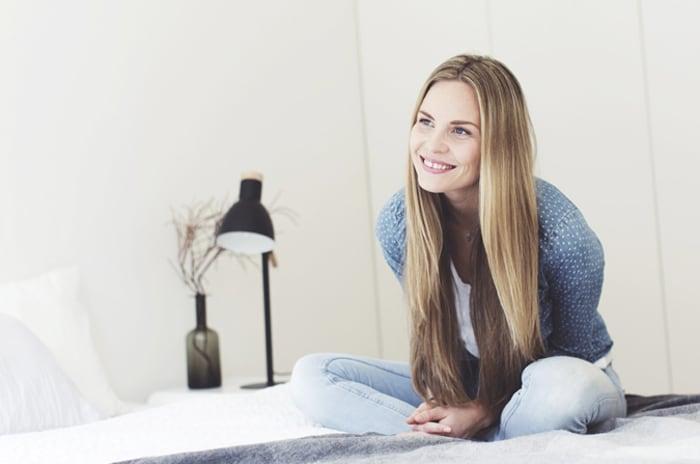 Smilende kvinne som sitter med bena i kors på senga