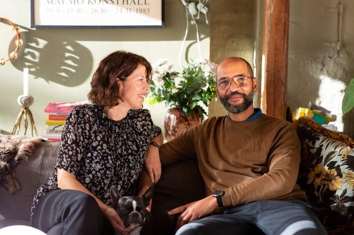 Et par sitter i sofaen og smiler