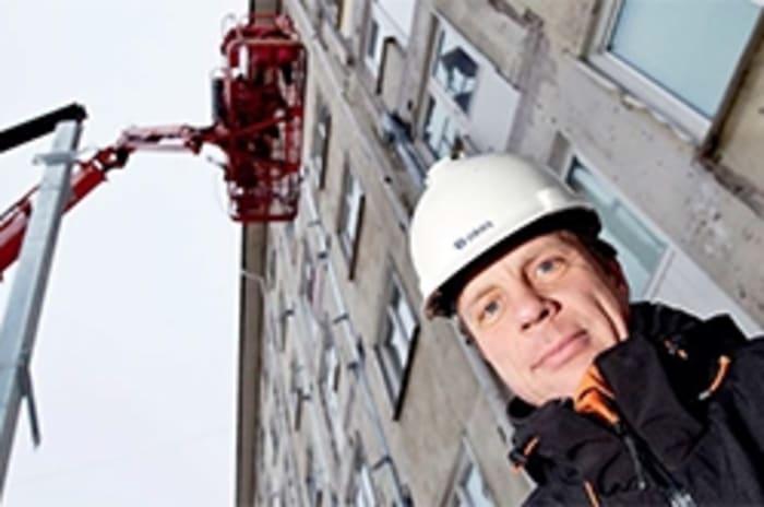 Bilde av mann med hjelm foran en høy bygning