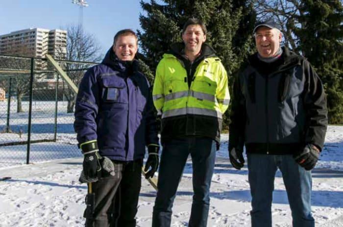 Bilde av tre menn som står utendørs i snøen og smiler