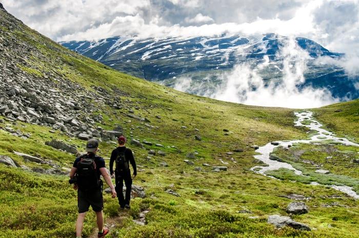 To menn som går i fjellandskap.