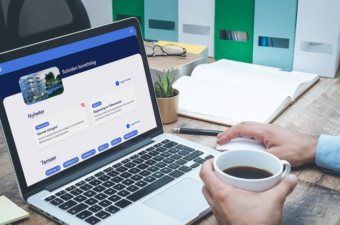 Vibbo vises på en laptop hjemme hos en person som drikker kaffe