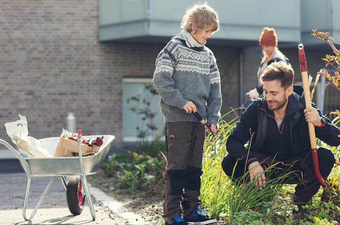 Gutt ved siden av trillebår og med mann med spade i hånden bidrar med dugnadsrbeid i blomsterbedd
