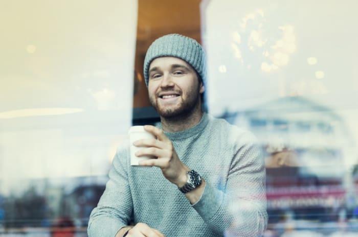 Bilde av en mann som sitter på kafé og drikker kaffe