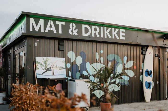 """Bilde av et bygg på visningssenteret på Fornebu. På bygningen står det """"MAT & DRIKKE""""."""