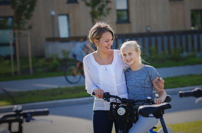 Bilde av mor av datter som smiler og sykler.