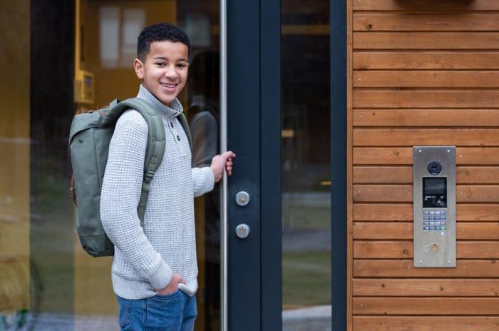Gutt som holder i en utgangsdør