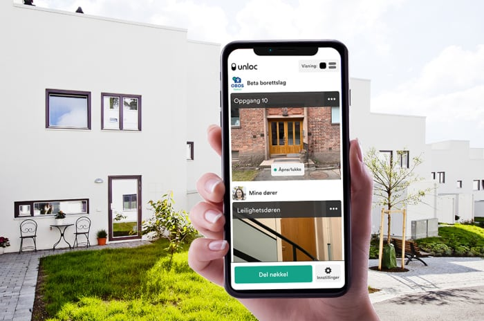 Bilde av en hånd som holder en mobil med Unloc appen foran noen boliger