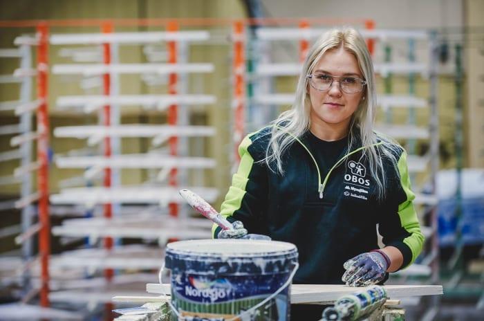 En ung tjej står med en färgburk och målar på en OBOS-fabrik