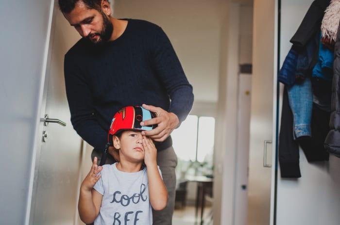 Man sätter hjälm på barns huvud obos