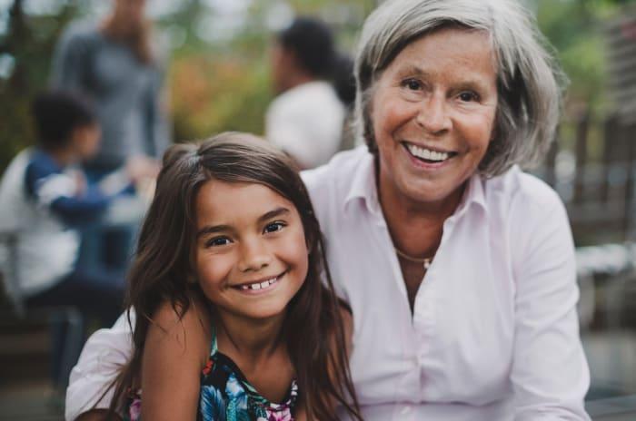 Seniorer och barnbarn som ler