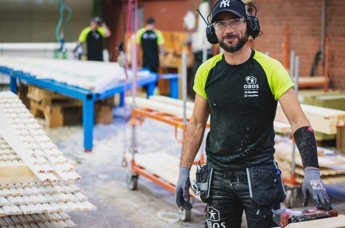 en arbetare på obos som jobbar med trä