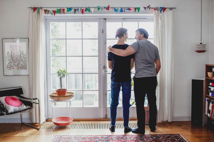 två män står och tittar ut genom en glasdörr med ryggarna mot kameran