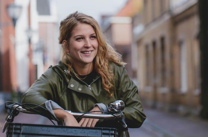 Kvinna som ler och lutar sig mot cykelstyret på en mindre stadsgata.