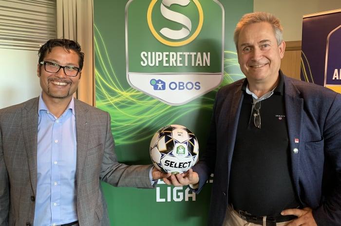 Två män står och håller en fotboll framför en superettan-vimpel.