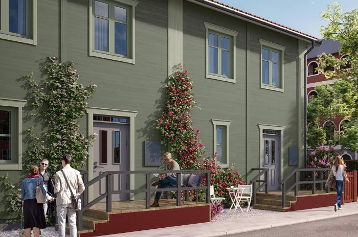 Två personer står på gångvägen utanför en tvåvånings-lägenhetshus