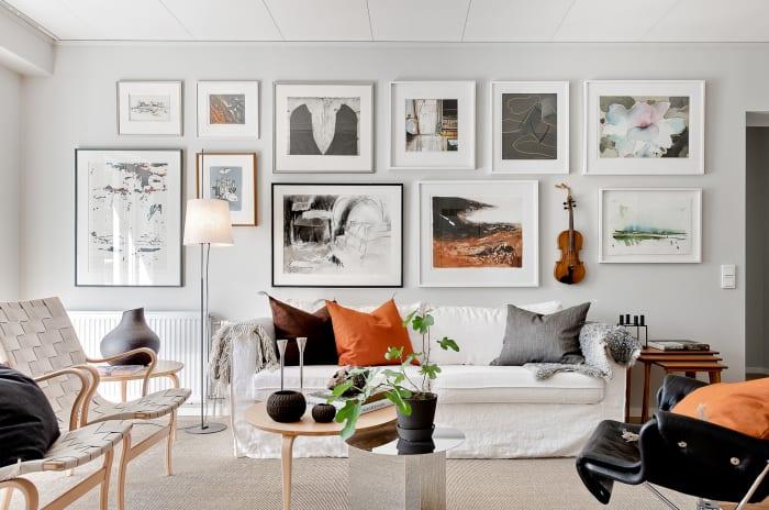 en soffa framför en vägg av tavlor