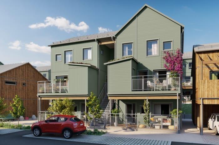 grönt lägenhetshus med balkonger