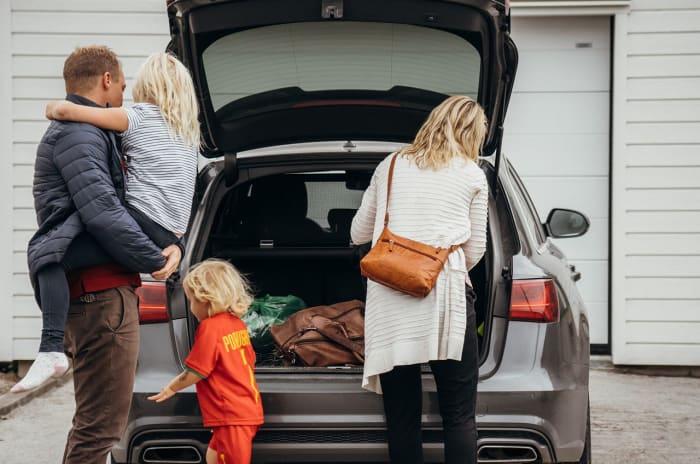 Ryggtavlor på tvåbarnsfamilj som packar ur en backlucka på svart bil