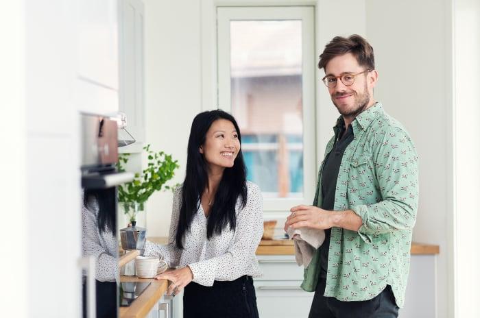 Ett par står i kök i ny bostad från OBOS
