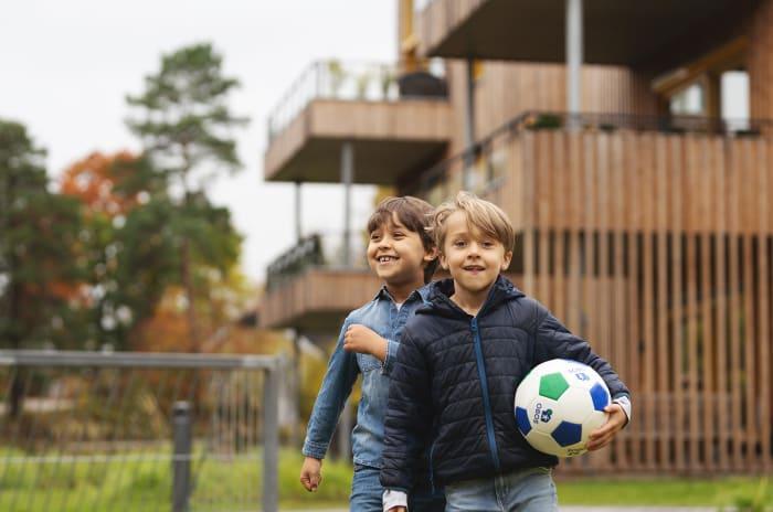 Två killar bär fotboll utanför OBOS-bostäder