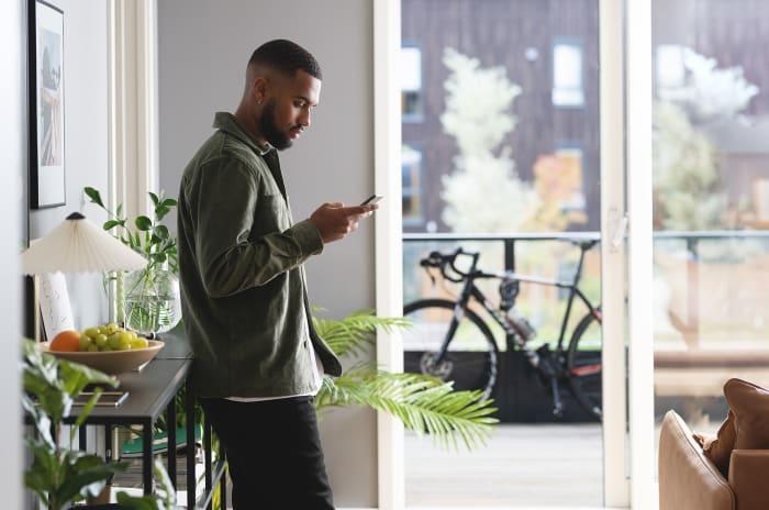 Ung man kollar står i ljust vardagsrum och kollar på mobil i hand