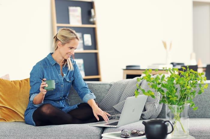Kvinna sitter uppe i soffa och dricker te och surfar på sin laptop