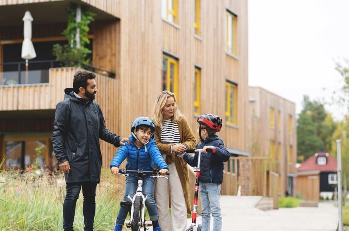 En familie med barn på sykkel og sparkesykkel foran boligblokk