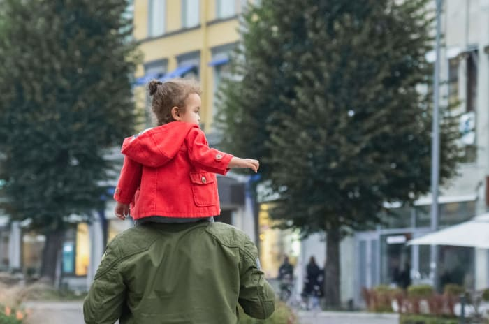 En flicka som sitter på sin pappas axlar