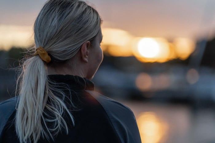 En kvinna som blickar ut över ett hav samtidigt som det är skymning