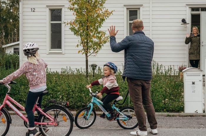 En pappa och två barn med cyklar utanför ett hus
