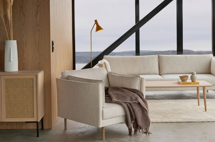 Stue innredet med sjenk, stol og sofa i lyse nordiske farger