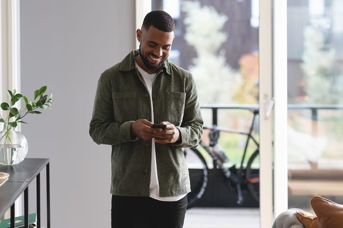 Illustrasjonsfoto av mann i stue med mobil i hånden.