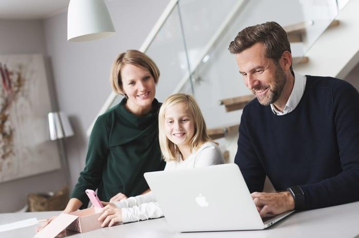 Mor, datter og far ser på en pc
