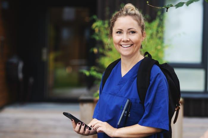 Sykepleier står utenfor en dør med en telefon i hånda