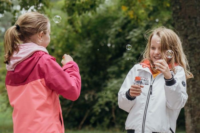 Två flickor som blåser såpbublor i en fantastisk miljö