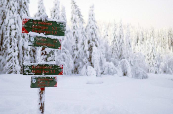 Skilt over turstier i vinterlandskap