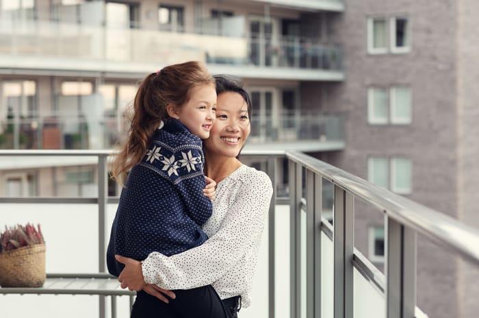 Mor som holder datteren sin på en balkong forkjøpsrett