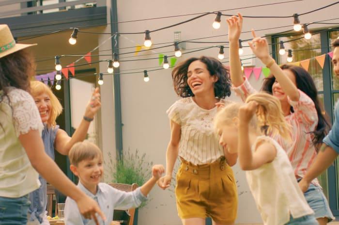 Barn og voksne som danser og ler utenfor en blokk