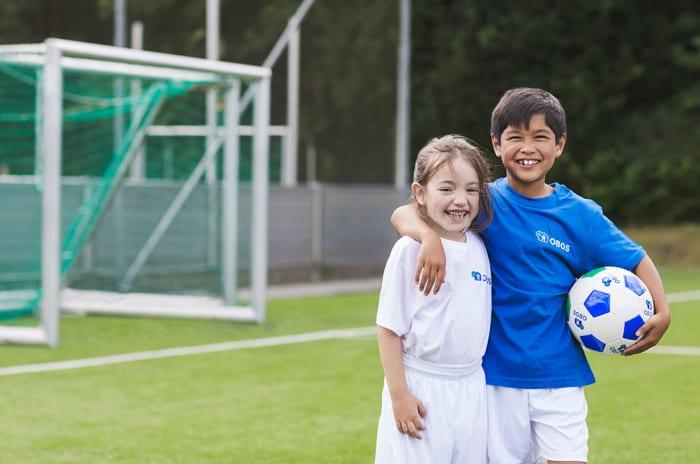 Jente og gutt på en fotballbane som smiler til kamera