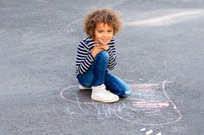 Jente sitter på asfalt med kritttegning
