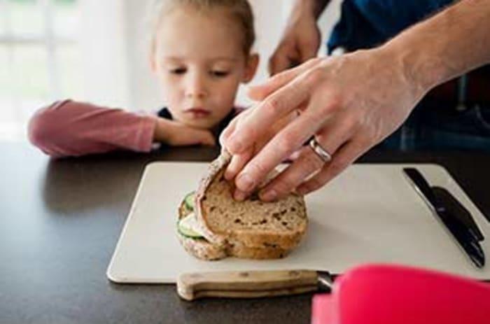 Voksen person smører en matpakke foran et barn.