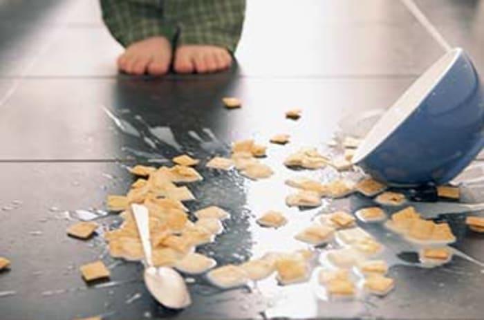 Bilde av et barn som har mistet frokostblandingen i gulvet.