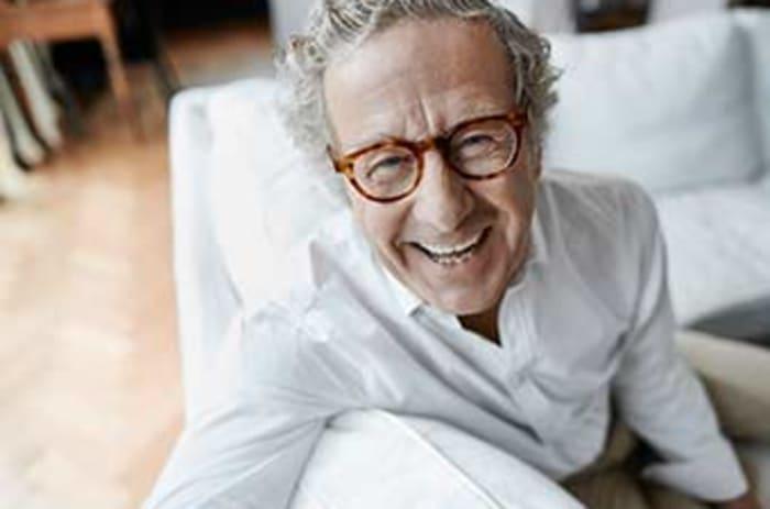 Smilende eldre mann med briller sitter i en sofa.