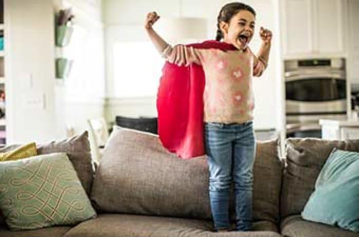 Liten jente med superheltkappe står i en sofa med armene opp.