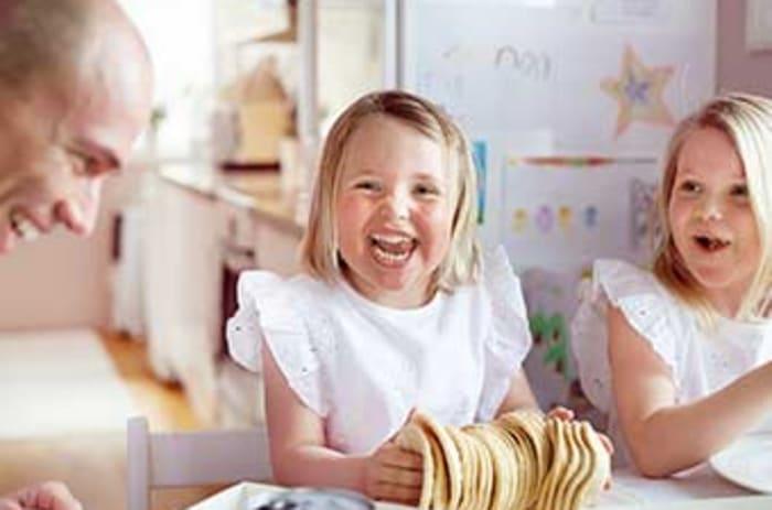 To smilende jenter sitter ved et bord og spiser terteskjell.