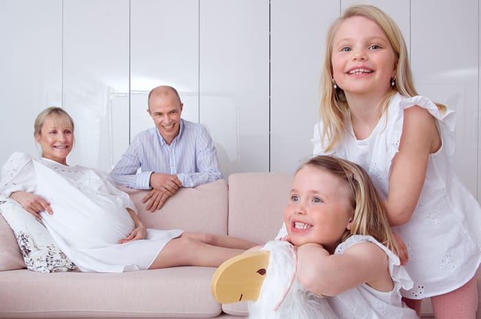 To unge jenter leker på en gyngehest i forgrunnen, mens en gravid kvinne og mann sitter på en sofa i bakgrunnen.