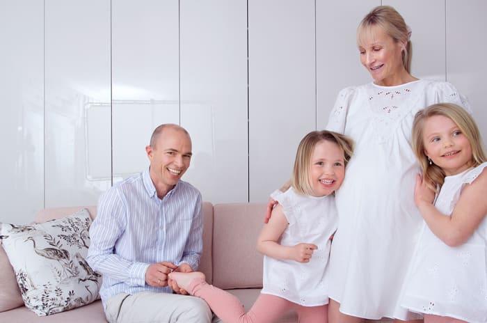 En familie på fire, med en mann, en gravid kvinne og to barn.