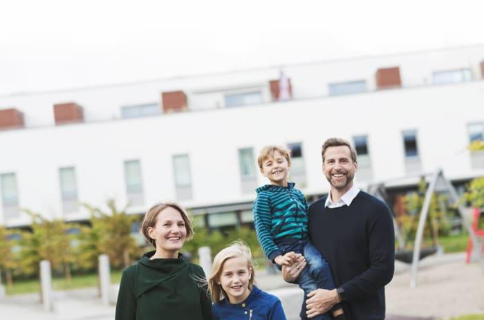 familj framför flerfamiljshus